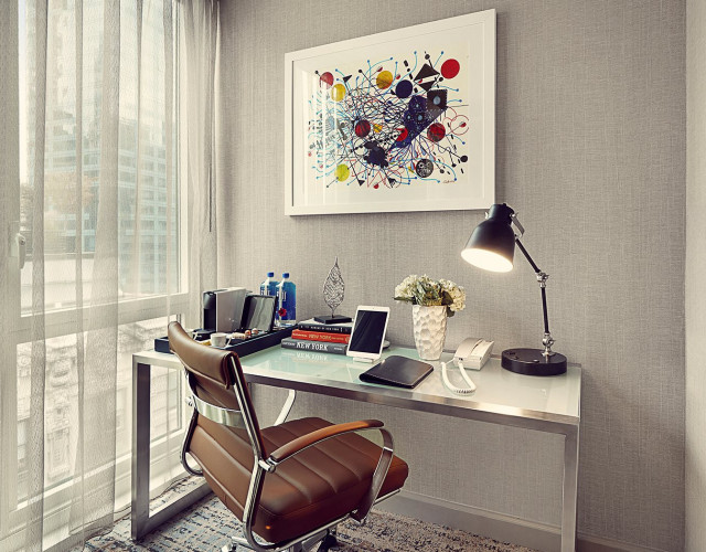 modern desk with a telephone, lamp and coffeemaker next to a large window.