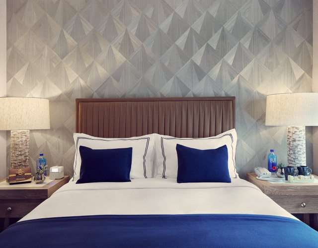 hotel room bed with blue and white pillows.