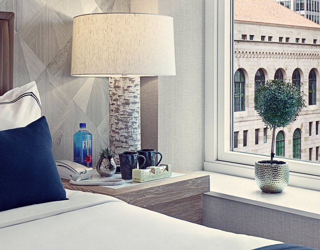 Hotel room nightstand with a telephone, two coffee mugs, cookies and lamp by a window