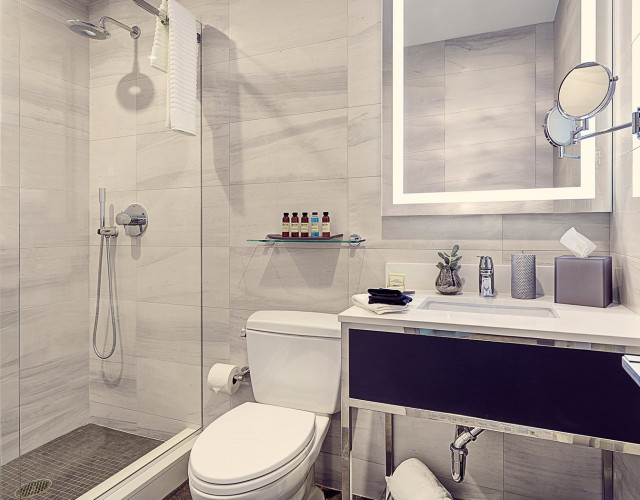 hotel bathroom with a glass door shower and a white vanity with towels and toiletries