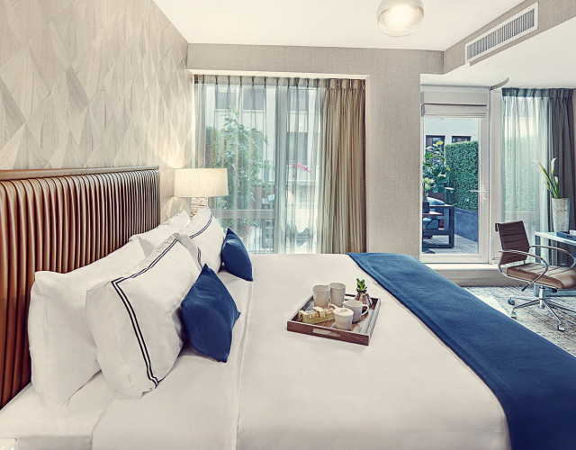 A spacious hotel room with a king bed, TV, desk, and glass door that opens to a private terrace