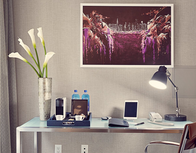 A modern desk with flowers, lamp and coffeemaker on top it.