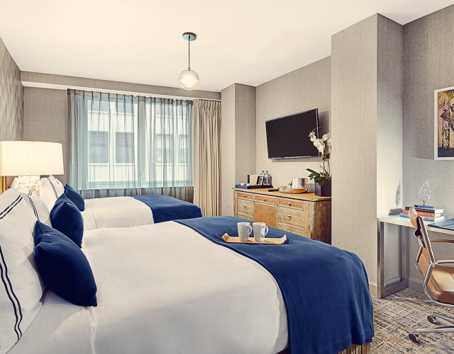 two queen bed hotel room with a large window, modern desk and chair, armoire and TV