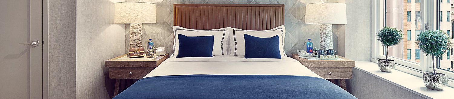 A queen bed with white and blue pillows with a nightstand on each side
