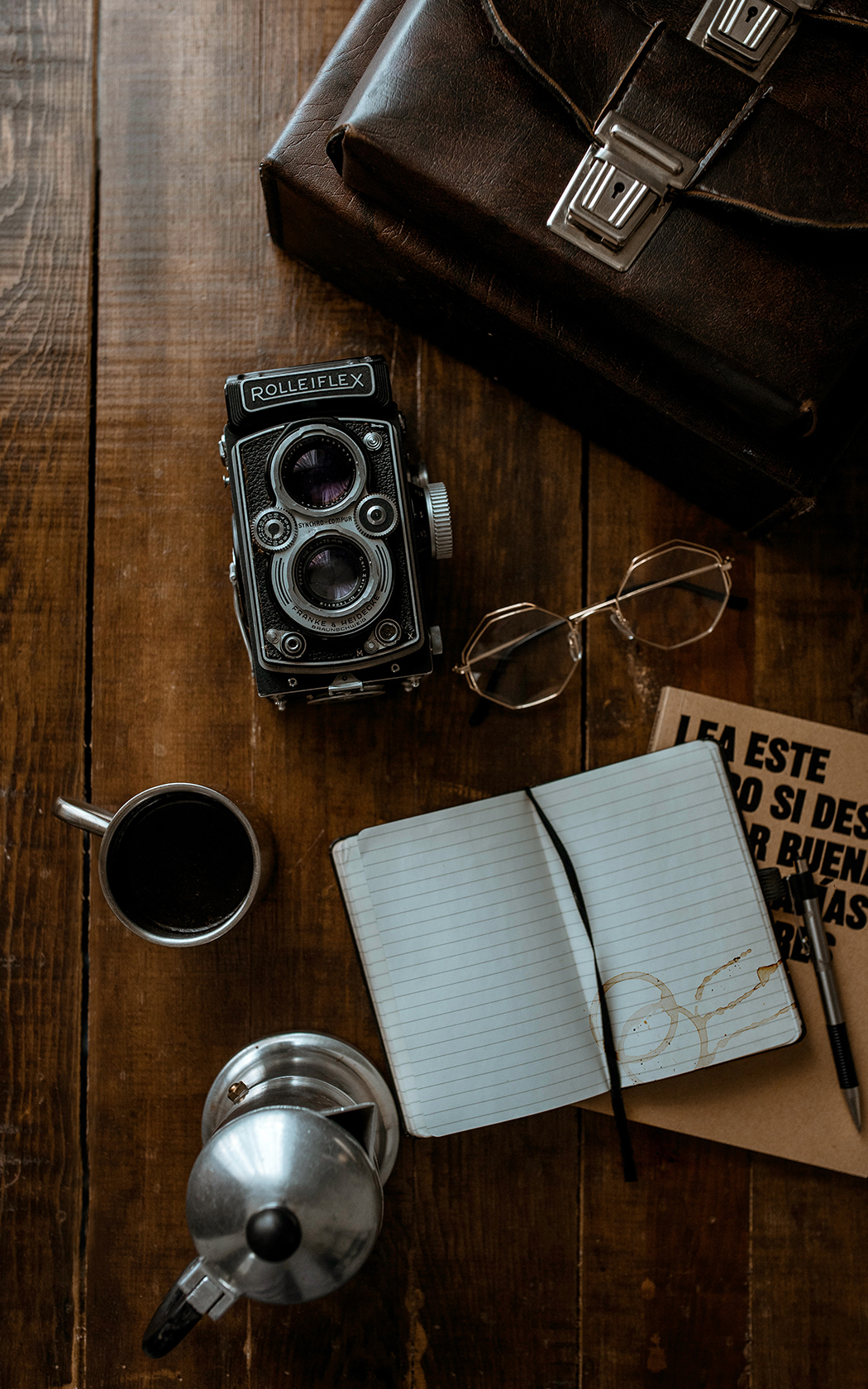 overhead view of a notebook, coffee cup and camera