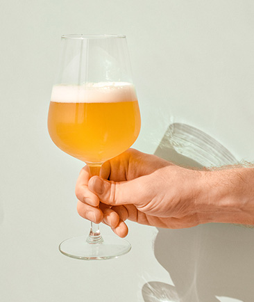 person holding a glass of beer in front of a pale green wall