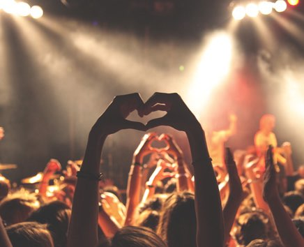 person making a heart shape with their hands at a concert