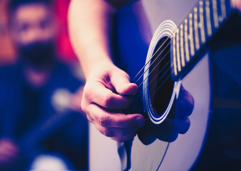 close up of a person playing the guitar