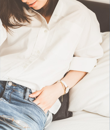 woman wearing jeans and white button down sitting on a bed