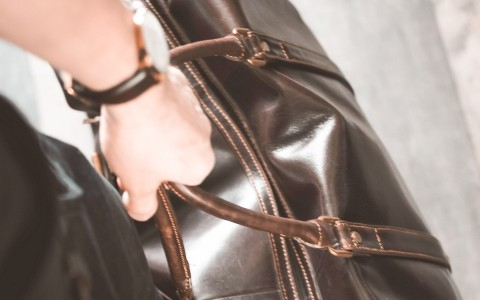close up of a man holding a leather carry on bag