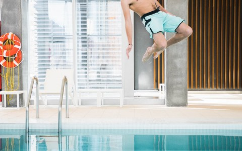 boy in the air about to splash into the water at an indoor pool