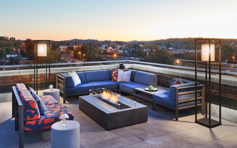 rooftop bar with a fire pit and blue couches