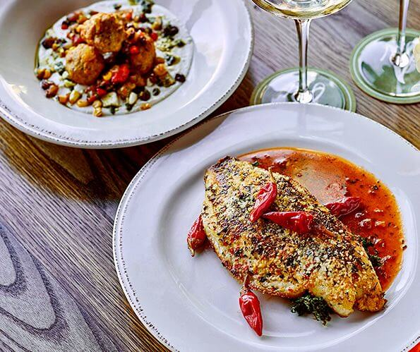 fish filet with red peppers on a white plate