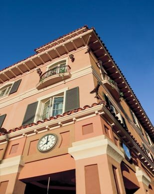 peach building with clock and spanish tile roof
