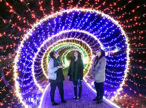 three women standing in a tunnel made of lights