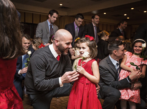 Man handing little girl wearing a red dress a flower