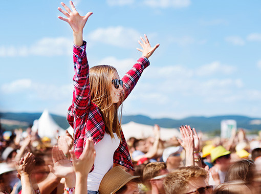 girl with her hands in the air at a concert