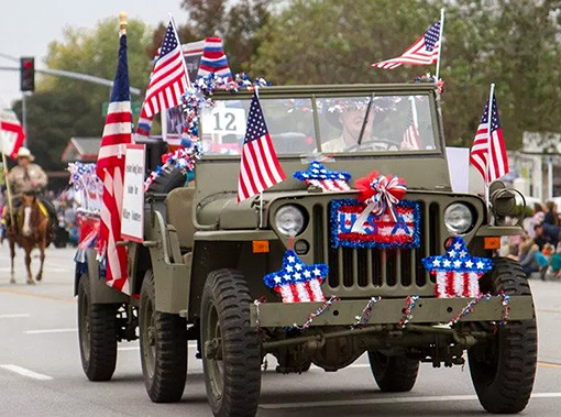 army colored jeep covered in american flags