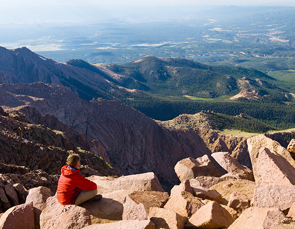 man in red shirt sitting on mountain summit looking at the views below