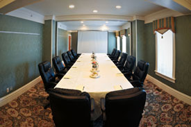 long table in boardroom with black chairs