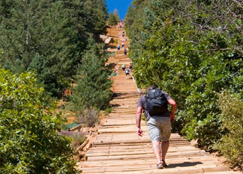 View of Pike's Peak Manitou Incline trail, a line of people are hiking up the path