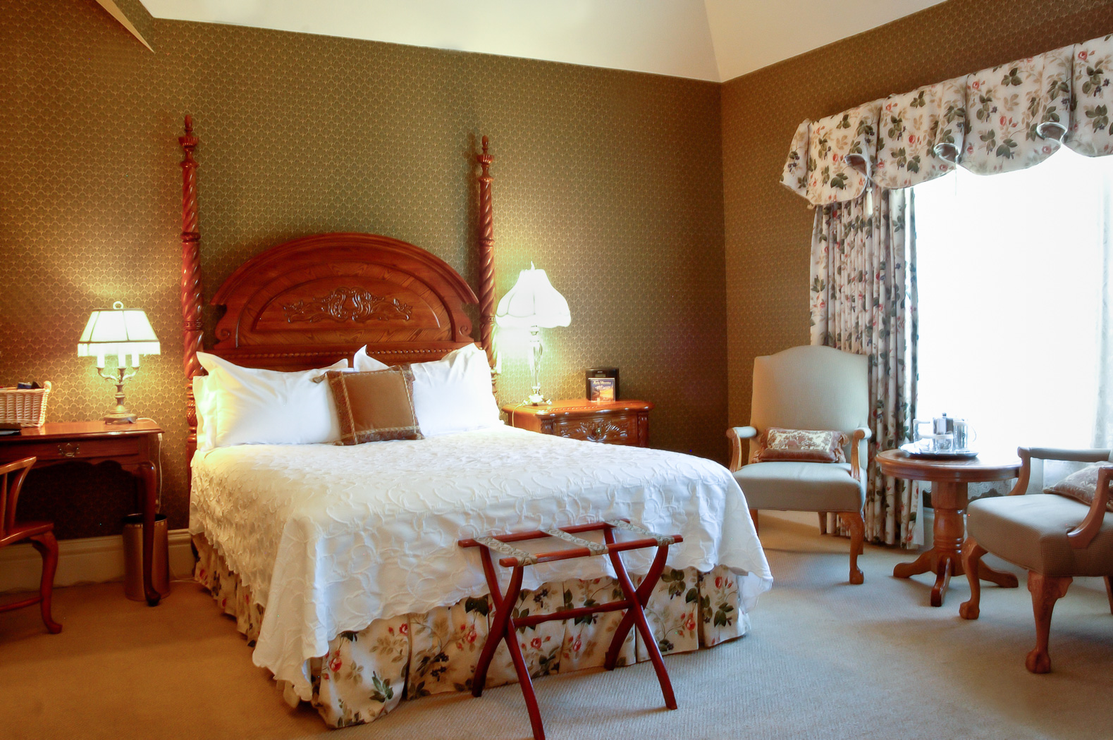 view of bedroom with white bed and floral accents, two nightstands with lamps, two lounge chairs with table