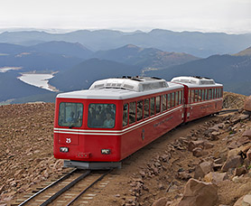 a red train on a track going through mountains