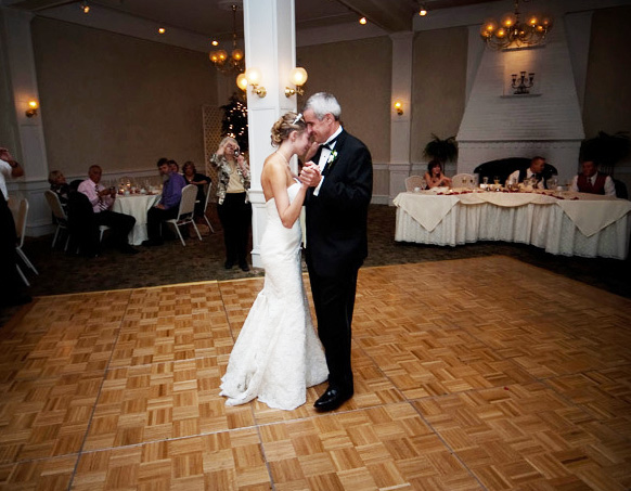 Bride and father dancing in ballroom