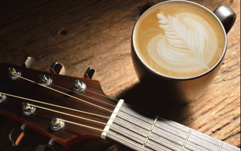 Coffee in a cup next to a guitar