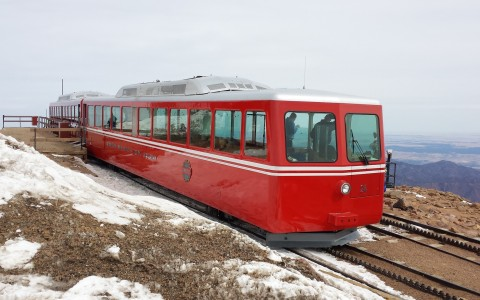 Pikes Peak Cog Railway red train on snowy mountainside