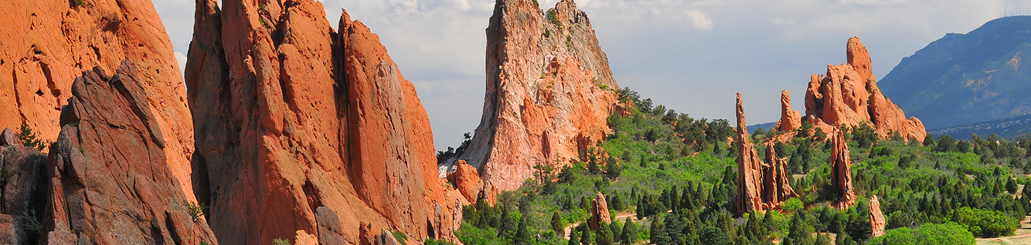 view of orange rock formations, green trees and blue sky