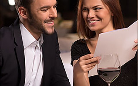 a couple looking at a menu and enjoying salads and a glass of red wine