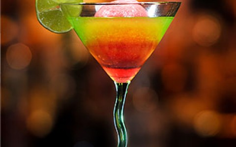 a martini glass with a green and pink drink and a lime garnish
