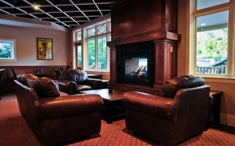 seating area with fire place, brown leather couches, coffee table