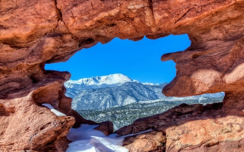 View through red rock formation onto a snow capped mountain in the distance