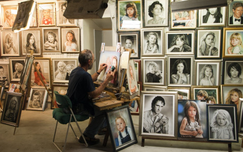 artist works on a portrait outside