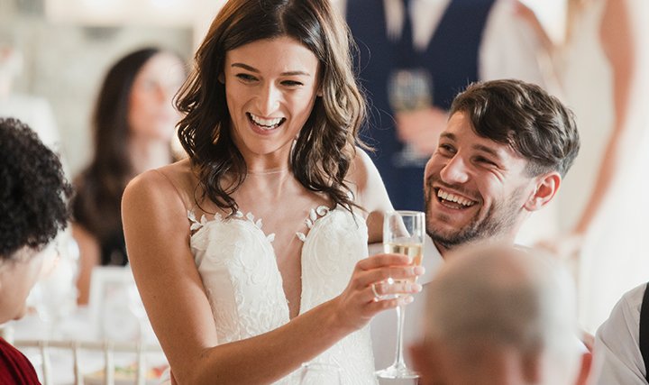 bride laughing with champagne in hand