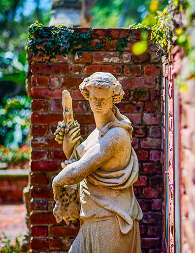 statue of greek woman with a brick wall with ivy on it in the background