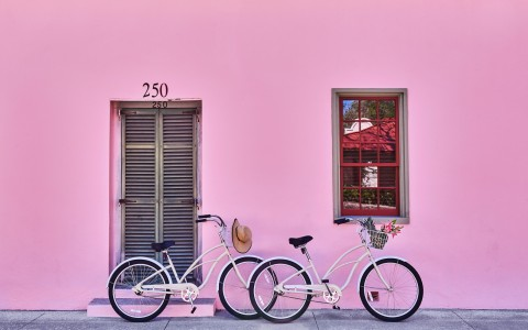 bikes leaning on a pink wall