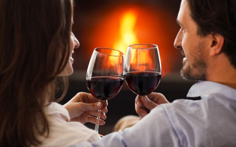 couple sitting by the fireplace drinking wine