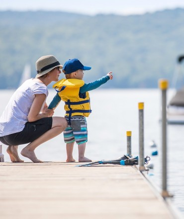 a man and his son watching boats on the dock