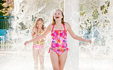 two girls splashing in outdoor pool