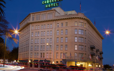crockett hotel with neon green sign on top lit up at night