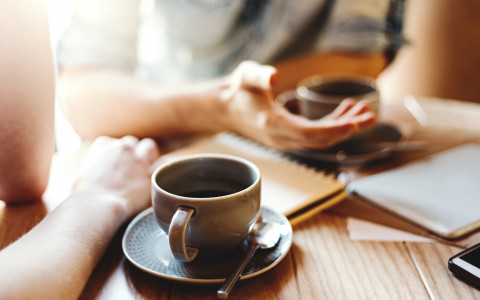 close up of two people having coffee together