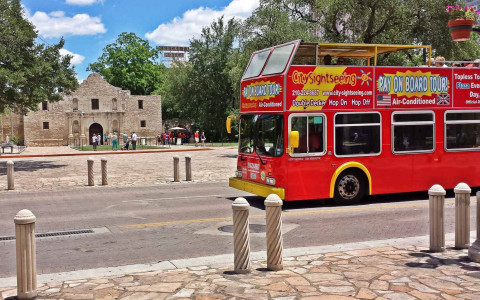 a red tourist bus driving in front of the alamo