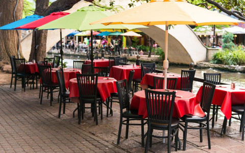 outdoor dining tables along the riverwalk with colorful umbrellas