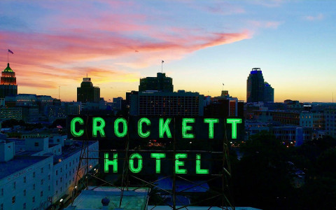 neon green crocket hotel sign on top of the building at night