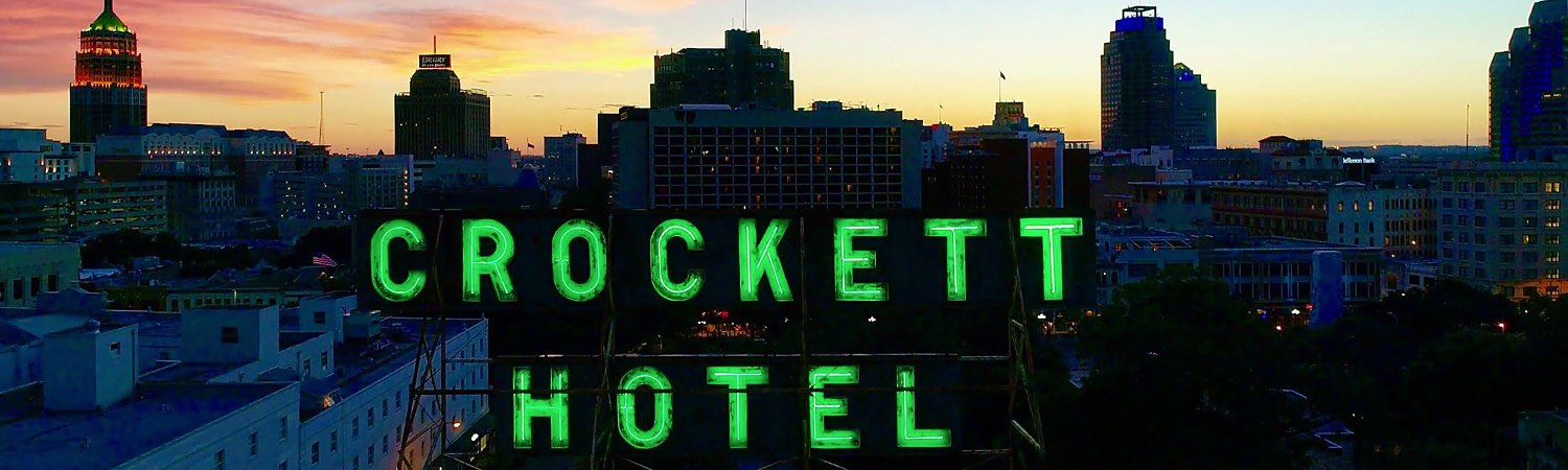 neon green crockett hotel sign lit up at night