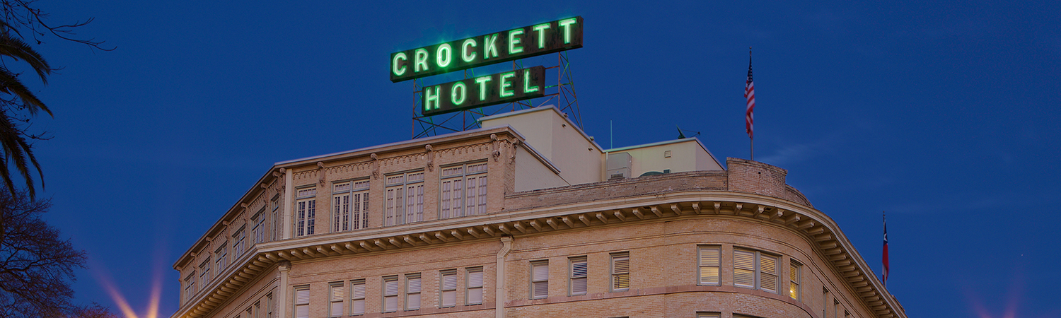 a neon green crockett hotel sign on top of the hotel