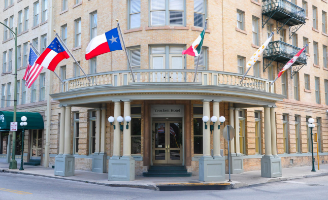 Hotel entrance with flags waving in the wind above it